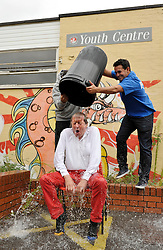© Licensed to London News Pictures. 26/08/2014; Bristol, UK.  George Ferguson, elected Mayor of Bristol, takes the ice bucket challenge at the Mill Youth Centre run by Empire Fighting Chance.  Chris and Jamie Sanigar of Empire Fighting Chance pour iced water over the mayor.<br /> Photo credit: Simon Chapman/LNP