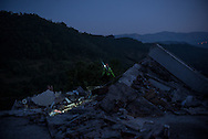 A rescuer inspect a collpsed building in Amatrice in the early morning, still many body are supposed to be found under the rubles.