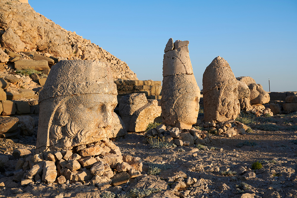 Statue heads, from left, Zeus, Apollo,  Herekles Eagle, & Lion with headless seated statues in front of the stone pyramid 62 BC Royal Tomb of King Antiochus I Theos of Commagene, east Terrace, Mount Nemrut or Nemrud Dagi summit, near Adıyaman, Turkey .<br /> <br /> If you prefer to buy from our ALAMY PHOTO LIBRARY  Collection visit : https://www.alamy.com/portfolio/paul-williams-funkystock/nemrutdagiancientstatues-turkey.html<br /> <br /> Visit our CLASSICAL WORLD HISTORIC SITES PHOTO COLLECTIONS for more photos to download or buy as wall art prints https://funkystock.photoshelter.com/gallery-collection/Classical-Era-Historic-Sites-Archaeological-Sites-Pictures-Images/C0000g4bSGiDL9rw