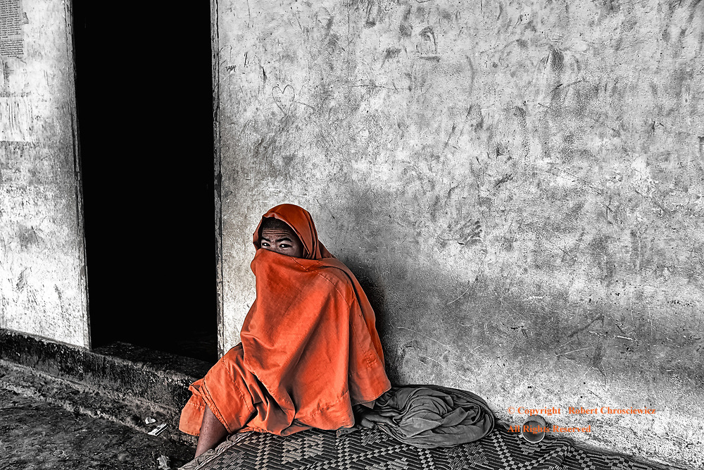 Hiding (B&W&C): A young Buddhist monk sitting outside of his run down and dirty residence, expresses his modesty by hiding his face behind a robe, Muang Sing Laos.                                                                                                                                                                                                                HL: A Buddhist monk hides behind his robe, Muang Sing Laos.