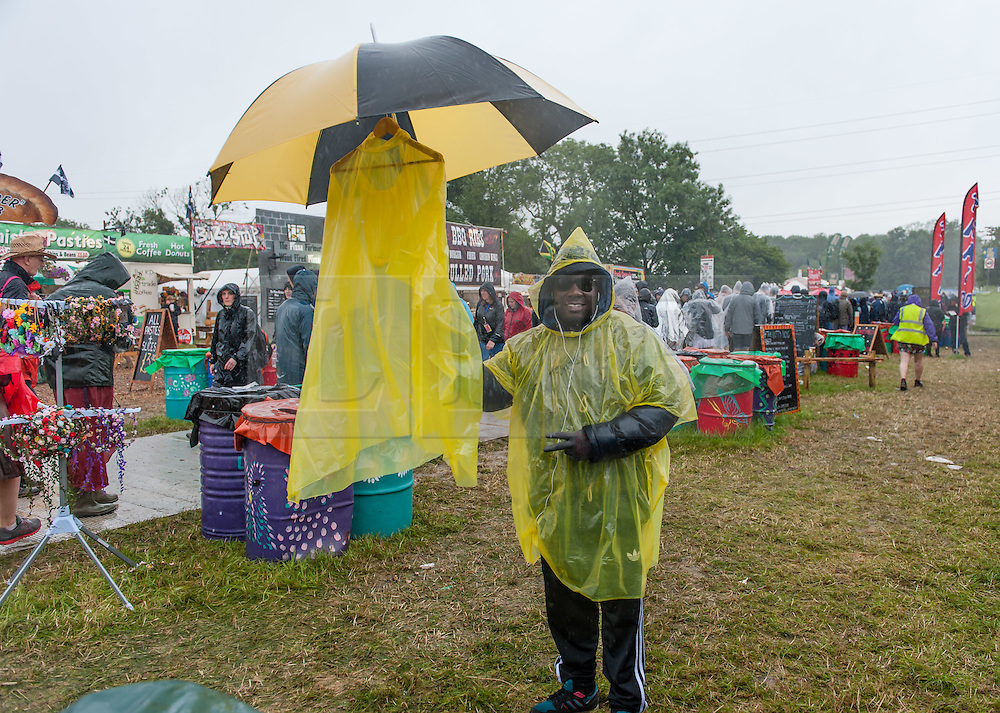 © Licensed to London News Pictures. 26/06/2015. Pilton, UK.  Rain and mud at Glastonbury Festival 2015 on Friday Day 3 of the festival - a plastic poncho seller does a brisk trade.  This years headline acts include Kanye West, The Who and Florence and the Machine, the latter being upgraded in the bill to replace original headline act Foo Fighters.   Photo credit: Richard Isaac/LNP