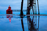 The Sturgeon Bay, Wisconsin lighthouse reflects on water on a pier leading out to the lighthouse at dawn on Lake Michigan. Photo by Mike Roemer