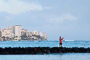 A fisherman casts of a jetty along Waikiki Beach in Hawaii.