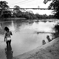 A prostitute baths in the river before going to work in one of the towns many brothels. In past times FARC rebels washed their uniforms here, Government negotiators held parties after new peace accords and now the bodies of victims of paramilitary assassination float past. The people of San Vicente continue to cross the suspension bridge as they go about their daily lives amidst the power struggles and changing fortunes of the town.<br />