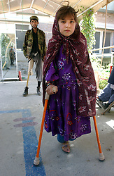 KABUL,AFGHANISTAN - SEPT. 11: An Afghan girl and man who lost their legs to explosive devices  learn to walk with at an ICRC hospital in Kabul, Afghanistan September 11,2002. While Americans are remembering the attack on the World Trade Center  one year ago today, most Afghans are trying to forget the decades old war which killed more than a million people here in Afghanistan. (Photo by Ami Vitale/Getty Images)