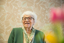 Portrait of a senior woman in front of wallpaper