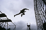 A Parachute Regiment recruit is in mid-flight and leaps across a wide space between scaffolding and a rope net during the 14-week long Pegasus (P) Company selection programme. Seen in silhouette, the man is in full stretch, half-way between the gantry he leapt from and the rope net that he is about to meet. It is an image that describes a mid-point, a half-way position between safety and uncertainty. Known as the Trainasium, it is an 'Aerial Confidence Course' which is unique to P Company. In order to assess his suitability for military parachuting, the Trainasium tests a candiates ability to overcome fear and carry out simple activities and instructions at a height above ground level. Recruits wanting to join the British Army's Parachute Regiment held regularly at Catterick army barracks, Yorkshire, need to pass this and other tests before earning the right to wear the esteemed maroon beret.