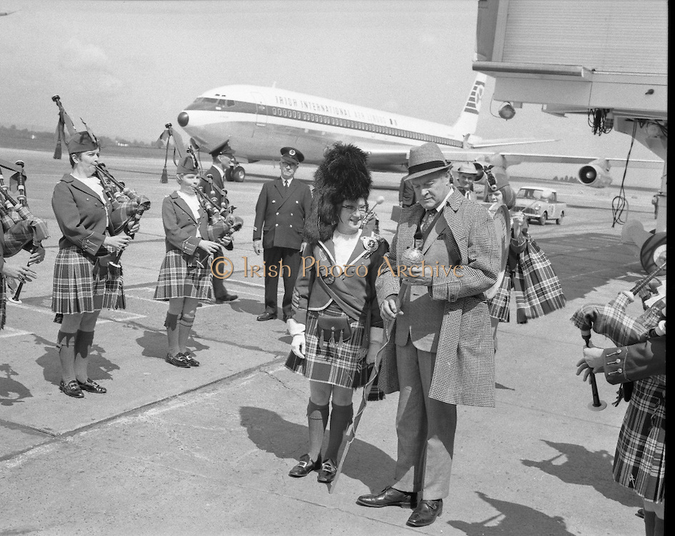 """Bob Hope, flying in to attend a showing of his film """"8 n the Run"""" at the Savoy Cinema, baffled the reception party there to meet him when he marched down between the rows of girls of the Emerald Girls Pipe Band and took over the mace from Drum Major Miss Marie Doran..18.05.1968"""