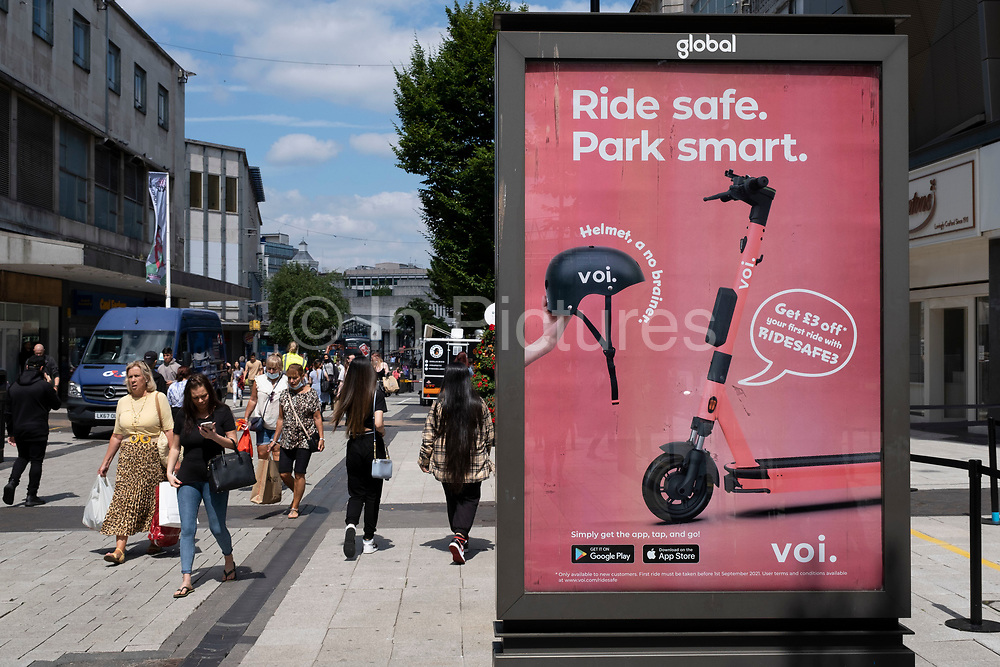 Voi eScooter hire advertising on 14th July 2021 in Birmingham, United Kingdom. A scooter-sharing system is a shared transport service in which electric motorized scooters, also referred to as e-scooters, are made available to use for short-term rentals. E-scooters are typically dockless, meaning that they do not have a fixed home location and are dropped off and picked up from certain locations in the service area.