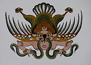 Representation of the immortal Garuda with a snake in his beak painted in traditional Bhutanese style on the wall of a house.  Garuda has the head, wings and lower body of a bird and the torso of a man. Garuda is the enemy of snakes and Nagas and they are usually seen grasped in his beak or claws. Also known as Bjachung, the devourer, Lord of Birds.  Paro, Druk Yul Kingdom of Bhutan. 11 November 2007.