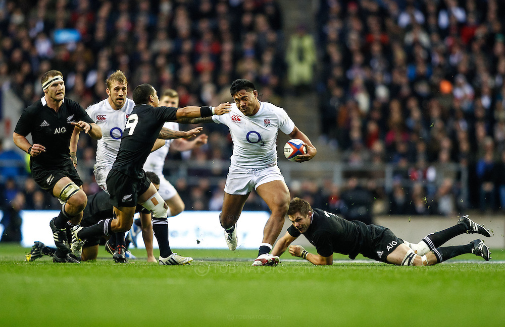 Picture by Andrew Tobin/SLIK images +44 7710 761829. 2nd December 2012. Manu Tuilagi of England escapes Richi McCaw's tackle and hands off Aaron Smith during the QBE Internationals match between England and the New Zealand All Blacks at Twickenham Stadium, London, England. England won the game 38-21.