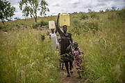 Rebecca Agani, foreground, and Nyatut Jok, at left, carry water buckets after fetching the water from a water pump in Bidibidi refugee settlement in Uganda. Rebecca was raped by five soldiers in June 2016 in Juba and gave birth to a daughter in 2017. She is living with seven children in Bidibidi camp including the daughter who was born out of rape.