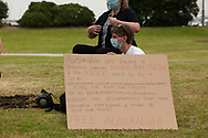 A male protester wearing a mask sits with a sign talking about the abuse of powers by police. After over 3 months of covid-19 lockdowns in Melbourne the easing of restrictions, allowed a small group of protesters to gather on St Kilda beach to protest police handing of demonstrations during the lock down. (Photo by Michael Currie/Speed Media)