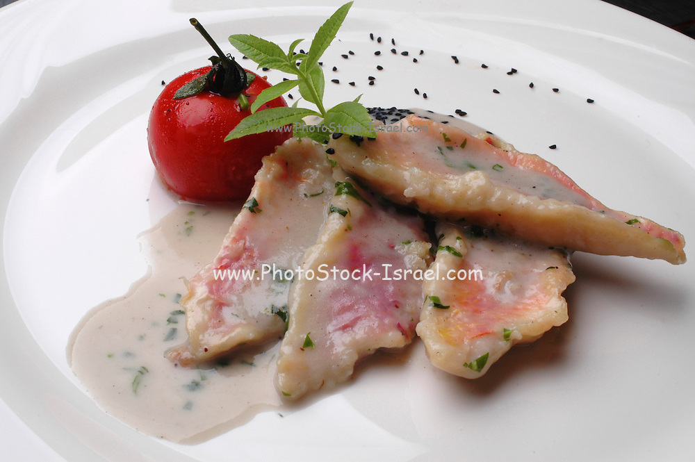 A serving of fish fillet garnished with Tomato and mint leaves