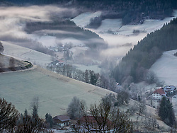 Winter morning in the valley of Yach with fog and farmhouse