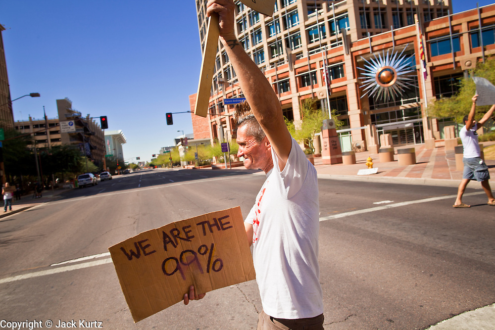 """22 OCTOBER 2011 - PHOENIX, AZ:    An Occupy Phoenix protester crosses a street in downtown on his way to the Occupy Phoenix protest Saturday. The demonstrations at Occupy Phoenix, AZ, entered their second week Saturday. About 50 people are staying in Cesar Chavez Plaza, in the heart of downtown. The crowd grows in the evening and on weekends. Protesters have coordinated their actions with police and have gotten permission from the city to set up shade shelters and sleep in the park, but without tents or sleeping bags, which is considered """"urban camping,"""" instead protesters are sleeping on the sidewalk.       PHOTO BY JACK KURTZ"""