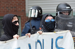 Protesters carry a sign under the watchful eye of riot police at a G7 protest in Quebec City, PQ, Canada on Thursday, June 7, 2018. Photo by Paul Chiasson/CP/ABACAPRESS.COM