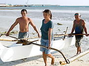 Fish vendor Imelda Esgana helps the fishermen carry their pump boat onto the beach, Talisay, Santa Fe, Bantayan Island, The Philippines. Every morning at 7 am Imelda meets the fishermen as they return from the sea with their catch. After sorting and weighing, Imelda sells the fish locally by going house to house. On November 6 2013 Typhoon Haiyan hit the Philippines and was one of the most powerful storms to ever make landfall. Three-quarters of the island's population of about 136,000 depend on fishing as their main source of income. Thousands lost their boats and equipment in the storm. Oxfam is working to support the immediate and long-term needs of affected communities on Bantayan Island including establishing boat repair stations.
