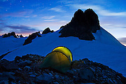 A tent glows below rocky spires and a starry sky at Klawatti Col, one of the most scenic climber high camps in North Cascades National Park, Washington.