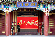"Chinese soldiers stand guard in front of the main entrance of Zhongnanhai, the home of China's leaders in central Beijing. The red script in Chaiman Mao Zedong's handwriting reads ""Serve the People"""