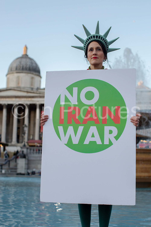 A woman wearing a Statue of Liberty hat whilst holding a sign saying No Iran War during a protest against U.S. President Donald Trump UK visit to attend the NATO North Atlantic Treaty Organisation summit on the 3rd December 2019 in London in the United Kingdom. Ahead of a British national election on 12th December 2019, Stop Trump Coalition and CND, Campaign for Nuclear Disarmament organised a protest to target a banquet at Buckingham Palace where Trump will dine with the Queen and other NATO leaders. The U.K. is hosting NATO summit to mark the military alliances 70th anniversary.
