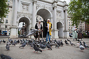 Two female tourists feed the pigeons in front of Marble Arch, Central London, United Kingdom.