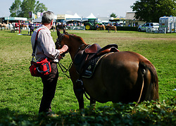 © Licensed to London News Pictures.16/07/15<br /> Harrogate, UK. <br /> <br /> A man stands and holds his daughter's pony ahead of a competition on the final day of the Great Yorkshire Show.  <br /> <br /> England's premier agricultural show has seen three days of showcasing the best in British farming and celebrating the countryside.<br /> <br /> The event which attracts over 130,000 visitors each year displays the cream of the country's livestock and offers numerous displays and events giving the chance for visitors to see many different countryside activities.<br /> <br /> Photo credit : Ian Forsyth/LNP