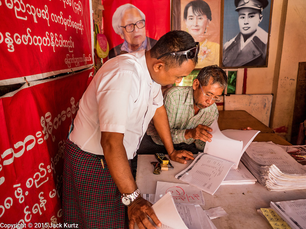02 NOVEMBER 2015 - YANGON, MYANMAR: A Burmese voter (left) looks for his name on a list of voters at a NLD campaign outreach office in Mingaladon, a township in Yangon. Photos of NLD leader Aung San Suu Kyi and her father, Gen Aung San, Myanmar's national hero, credited as being the father of Burmese independence are on the wall behind him. Voter registration rolls were released Monday. Voters and party officials are double checking rolls to ensure accuracy.  National elections are scheduled for Sunday Nov. 8. The two principal parties are the National League for Democracy (NLD), the party of democracy icon and Nobel Peace Prize winner Aung San Suu Kyi, and the ruling Union Solidarity and Development Party (USDP), led by incumbent President Thein Sein. There are more than 30 parties campaigning for national and local offices.     PHOTO BY JACK KURTZ