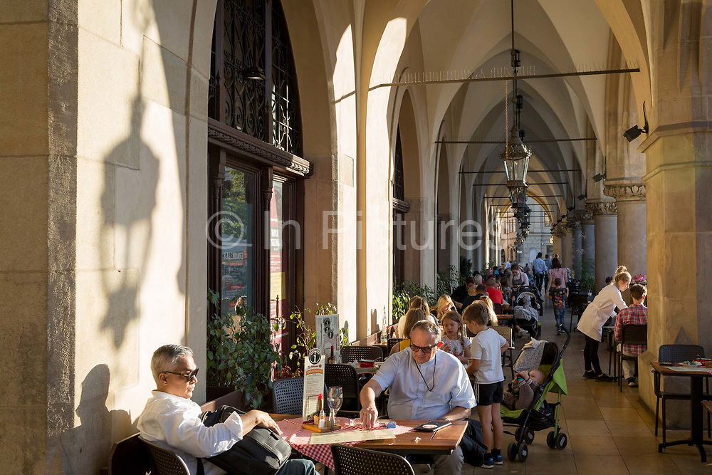 A priest enjoys sunshine in the arched passageway of the Renaissance Cloth Hall on Rynek Glowny market square, on 22nd September 2019, in Krakow, Malopolska, Poland.