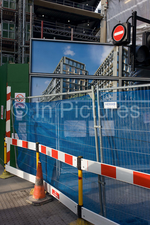 A street corner where temporary construction fencing and disruption has blocked off a City of London street. Blue netting in thius industrial fence is similar to the blue skies above the building as it will look in the future. The narrow part of a street called Wallbrook (the route of the ancient River Wallbrook that still flows underground here) is made even narrower due to the disruption in the part of the capital known as the Square Mile, London's financial and oldest heart.