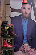 Dr Martens boots and construction hoarding featuring suited young man for dress hire business Moss Bros in central London. The footwear is placed on a rack outside in the street, a display of quality shoes known as a best-selling British brand sold around the world. The male model sits in smart clothing with tattoos on his hands.