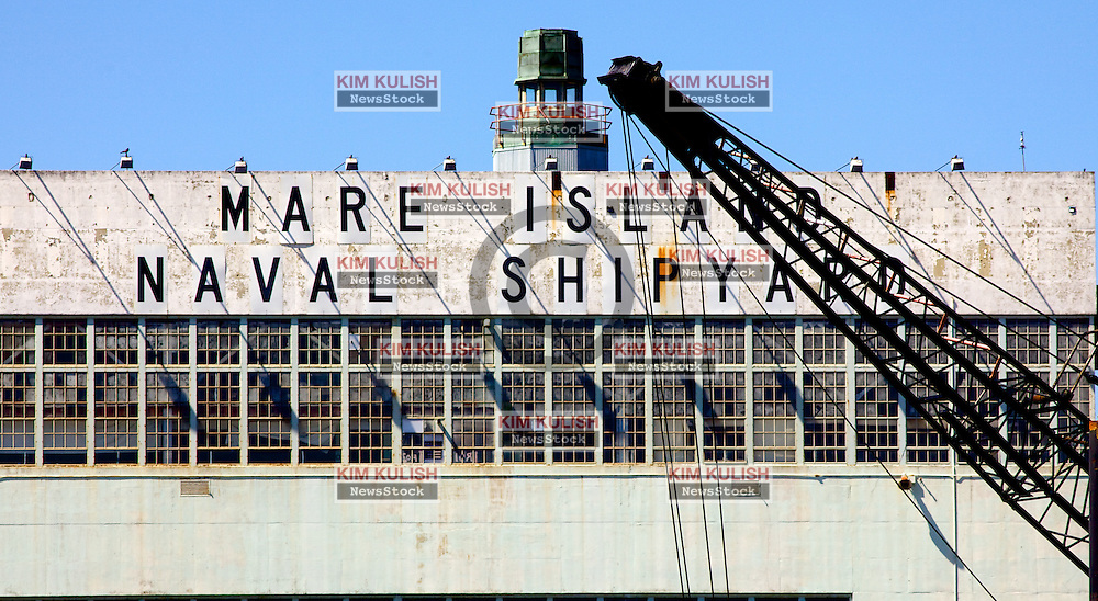 View of the Mare Island Naval Shipyard sign and crane along the waterfront in Vallejo, California.