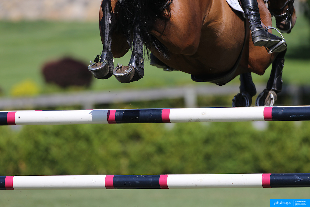 A horse and rider clear a jump during the $100,000 Empire State Grand Prix presented by the Kincade Group during the Old Salem Farm Spring Horse Show, North Salem, New York,  USA. 17th May 2015. Photo Tim Clayton