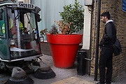 People on the streets interract with a large red plant pot in the City of London, UK. This situation creates a weird scale to this street scene a sa street cleaner passes.
