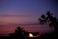 Group of people enjoying a campfire while watching the sunset on beach in the state of Michoacan, Mexico.<br />