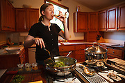 USA, Oregon, Eugene, young woman drinking wine while cooking dinner. MR