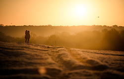 © Licensed to London News Pictures. 19/01/2020. London, UK. A couple watch sunrise in a frost covered landscape at sunrise in Richmond Park in west London on a bright and freezing Winter morning. Photo credit: Ben Cawthra/LNP