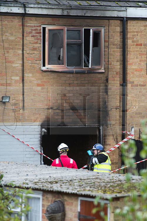 ©  London News Pictures. 15/10/2012. Harlow, UK. A fire investigation team examine damage at the rear of a property  on Barn Mead, Harlow, Essex where three children and a woman have died and three others are in hospital following a house fire. Two boys aged 13 and six, a girl aged 11 and the woman were declared dead at the scene. A nine-year-old boy and a three-year-old girl have serious burns and a man has minor burns. Photo credit : Ben Cawthra/LNP