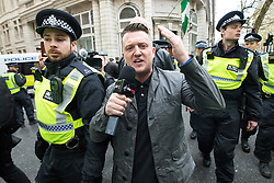 © Licensed to London News Pictures . 01/04/2017 . London , UK . Tommy Robinson on Northumberland Avenue , surrounded by police . The EDL and Britain First both hold demonstrations in London , opposed by anti-fascist groups , including Unite Against Fascism . Photo credit : Joel Goodman/LNP