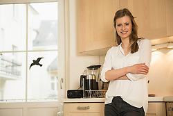 Young woman standing with arms crossed in kitchen and smiling, Munich, Bavaria, Germany