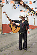An elderly cowboy musician poses with his guitar in Uruapan, Michoacan, Mexico.