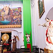 Statues and artwork in a side chapel of Iglesia de San Francisco, a Spanish colonial church in Antigua, Guatemala.