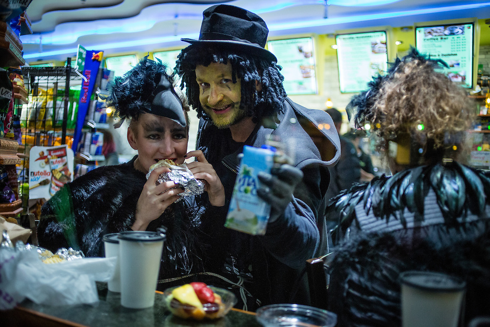 New York, NY - 31 October 2016. Two costumed parade goers seen through the window of a bodega on Thompson Street after the Greenwich Village Halloween Parade.