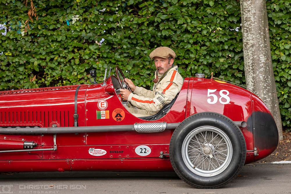 A driver smoking a pipe at the Goodwood Revival.<br /> Picture date: Friday September 17, 2021.<br /> Photograph by Christopher Ison ©<br /> 07544044177<br /> chris@christopherison.com<br /> www.christopherison.com<br /> <br /> IMPORTANT NOTE REGARDING IMAGE LICENCING FOR THIS PHOTOGRAPH: This image is supplied to the client under the terms previously agree. No sales are permitted unless expressly agreed in writing by the photographer.