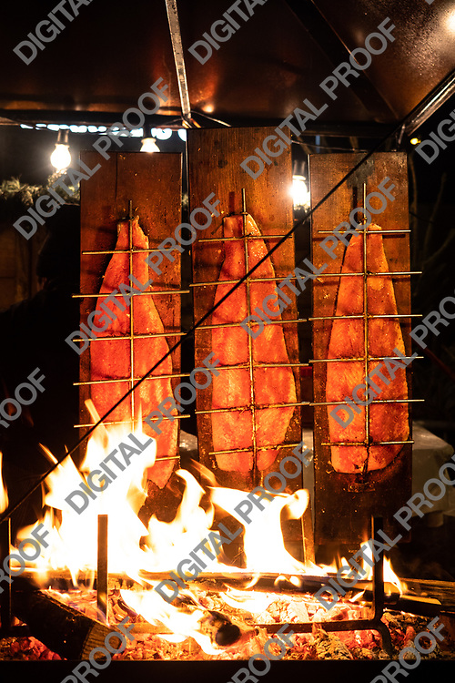 Zurich, Switzerland - December 22, 2018 detail of Salmons being smoked - cooked with wood planks in a food stand of the Christmas market held at Sechseläutenplatz