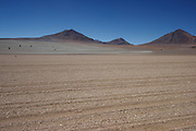 A tourist stops to investigate the Dali Landscape on the Bolivian Altiplano near the border with Chile