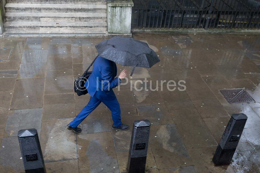 A man wearing a blue suit walks down Whitehall during seasonal rain showers, on 9th May 2019, in London, England.