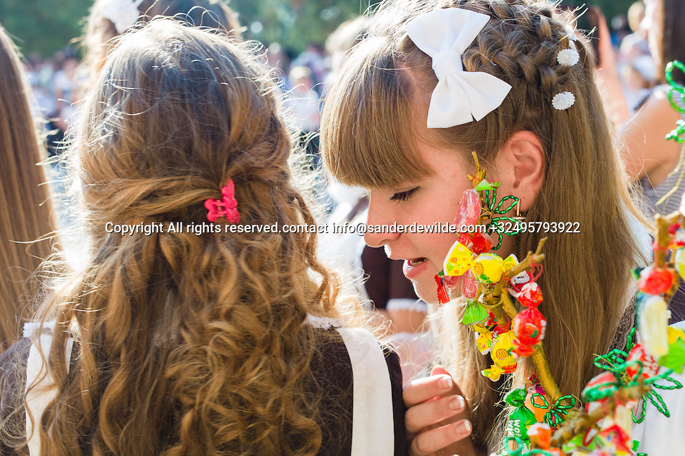 20150901 Moldova, Transnistria,Pridnestrovian Moldavian Republic (PMR) Tiraspol.Day of knowledge. First of september schools start and kids are dressed up in white and black. They brought flowers for their teachers.Oldest girls are dressed in Russian school uniforms.girls chat during speeches. They made a candy tree