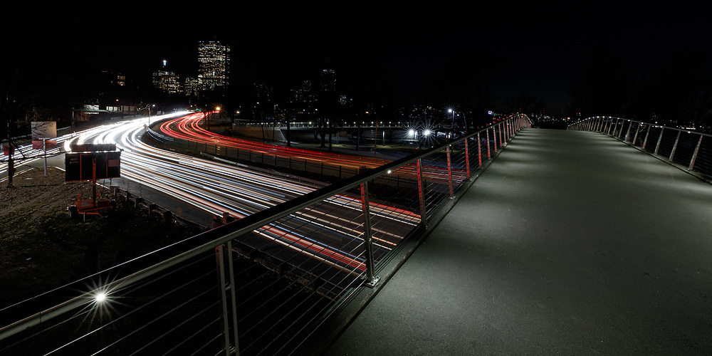 Cars driving along Storrow Drive on a cold winter evening in Boston.