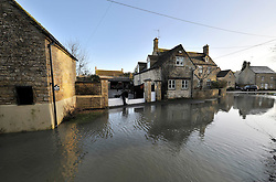 © Licensed to London News Pictures. 27 January 2013. Ascott Under Wychwood, Oxfordshire. Putting up the flood barriers. Floods rising to threaten properties. Floods after the snow melted. Photo credit : MarkHemsworth/LNP